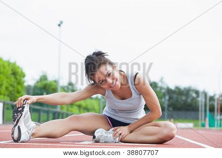 Brunette stretching her legs on on a track