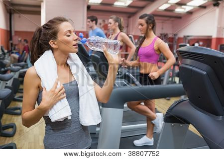 Woman drinking bottle of water in the gym after exercise on treadmill