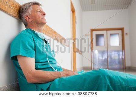 Tired surgeon is sitting on the floor in hospital corridor wearing green scrubs
