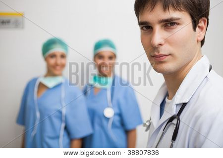 Satisfied doctor wearing labcoat with two smiling nurses wearing scrubs in background in hospital