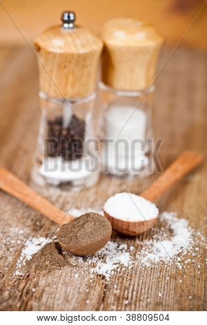 salt and pepper in spoons and shakers on rustic wooden table