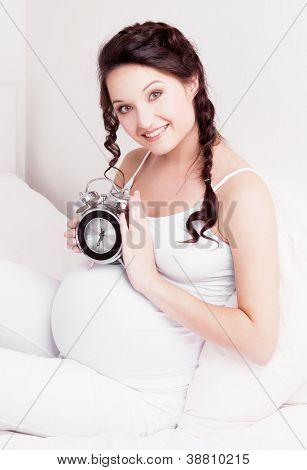beautiful young pregnant woman in bed at home