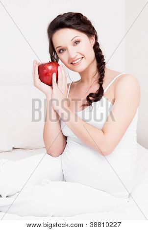 beautiful young pregnant woman eating an apple in bed at home