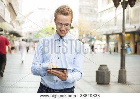 Homem de terno de negócio usando o computador tablet no espaço público