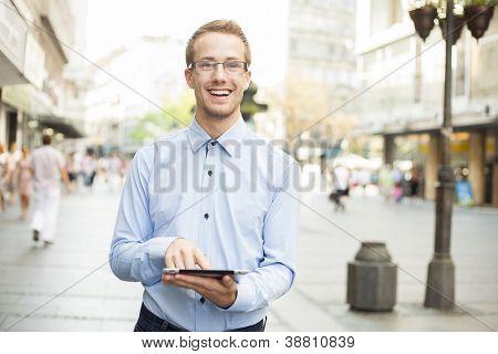 Sorridente empresário usando computador Tablet no espaço público e olhando na rua