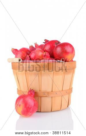 Pomegranates in a bushel basket. Vertical format on a white background with reflection.