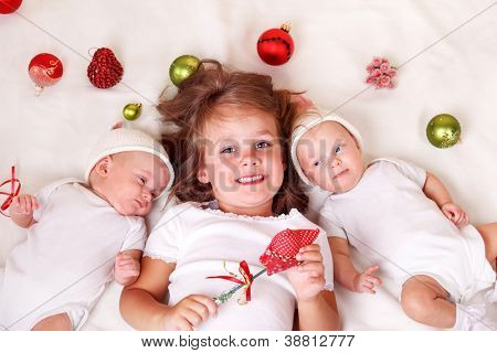 Siblings with Christmas decoration lie on bed