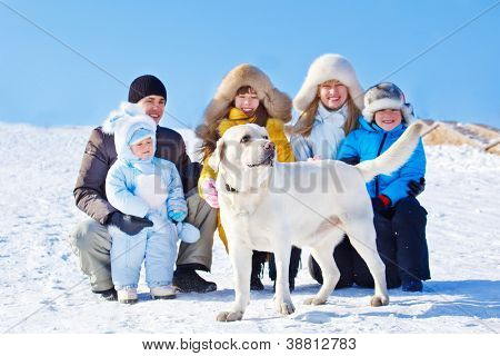 White winter labrador dog and family beside him