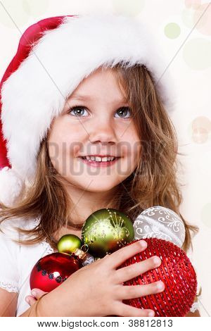 Sweet girl in Santa hat holding Christmas decoration in hands