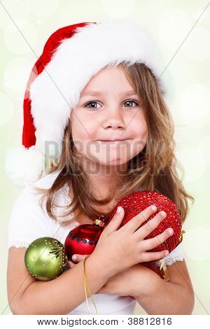Preschool girl in Santa hat holding Christmas decoration in hands