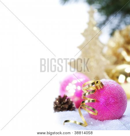 Pink christmas balls with decorations on a snow