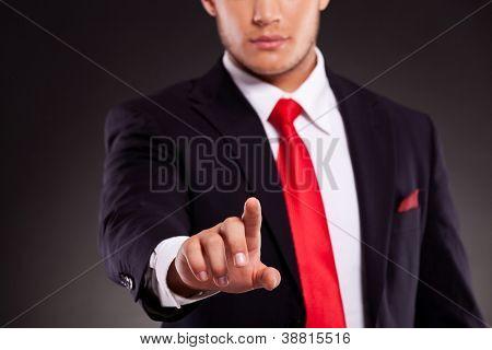 Ausschnitt Bild von einem jungen Geschäftsmann Knopfdruck mit Fokus auf seine Finger. gegen dunkle backg