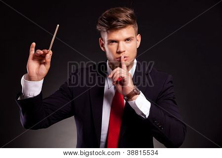young business man posing as a conductor who makes silence with his finger on his lips, on dark background