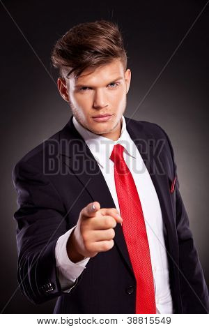 portrait of a young business man pointing at you, against a dark background