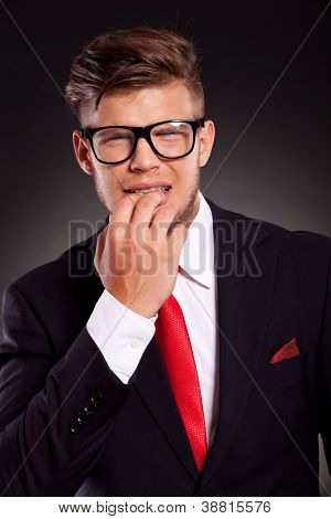 scared young business man with glasses bitting his nails, over dark background