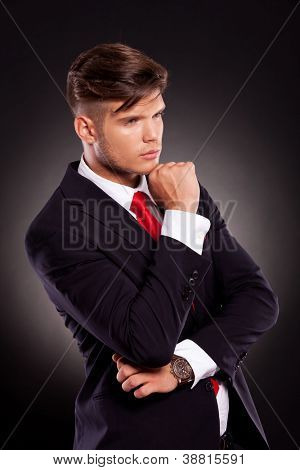 angle view of a pensive young business man looking away from the camera, on a dark background