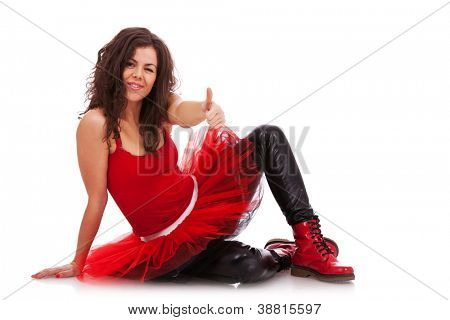 modern ballerina sitting on the floor, giving the thumbs up sign and winking