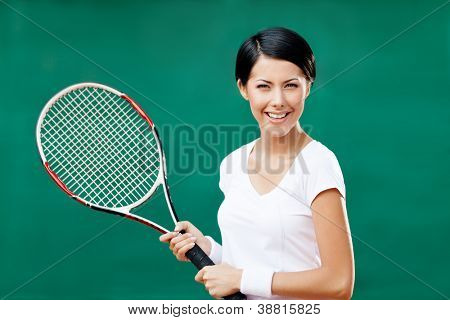 Portrait of successful female tennis player with racquet at the tennis court