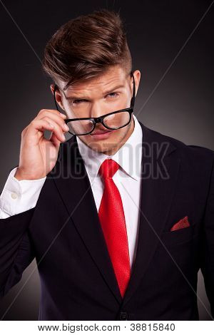 closeup portrait of a young business man taking off his eyeglasses, on dark background