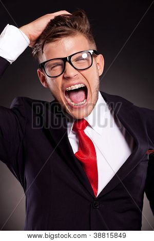 portrait of a desperate young business man shouting and pulling his hair. over dark background