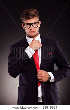 waist-up picture of a young business man fixing his tie and looking into the camera. on dark background