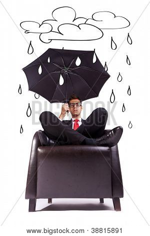 Image of a business man sitting in comfortable armchair with an umbrella in his hand - rainy days