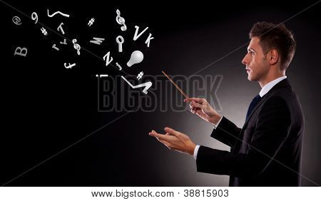 Side view of a young business man directing with a conductor's baton a bunch of symbols