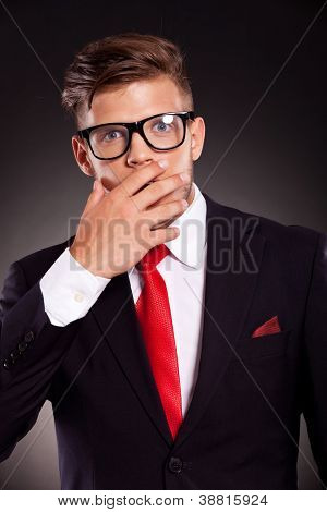 portrait of a young business man covering his mouth with his hand out of surprise. on dark background