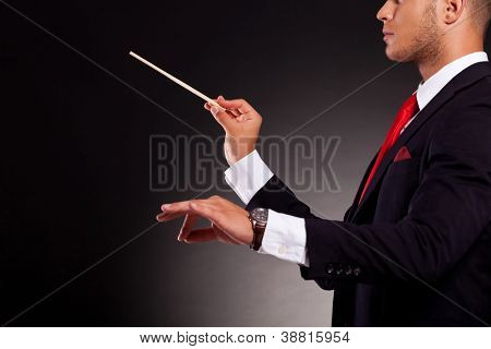 side view of a young business man conducting with a conductor's baton, on a dark background