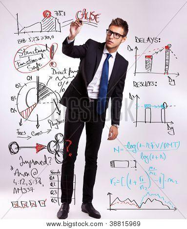 Foto de cuerpo entero de un hombre de negocios, dibujar o escribir algunos gráficos y diagramas con su marcador, pla