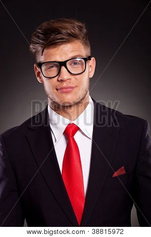 closeup of an arrogant young business man looking suspiciously at the camera with his eyebrow raised