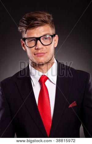 Closeup von eine arrogante junge Geschäftsmann misstrauisch in die Kamera schaut, mit seinen Augenbrauen angehoben