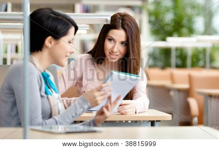 Two girls talk sitting at the desk at the library. Communication concept