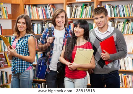 Group of happy students in a library
