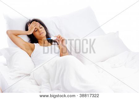 ill woman taking her temperature in bed wile feeling sick and with fever
