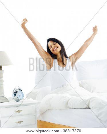 Mujer sueño cansada despertar y bostezo con un estiramiento mientras sentado en la cama aislado en blanco backg