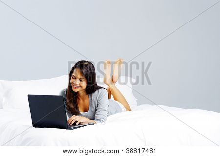 Laptop computer woman lying on bed, happy smiling and relaxing at home isolated on grey background