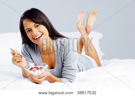 morning breakfast meal woman eating healthy yoghurt and fruit in bed while happy and smiling isolated on grey background