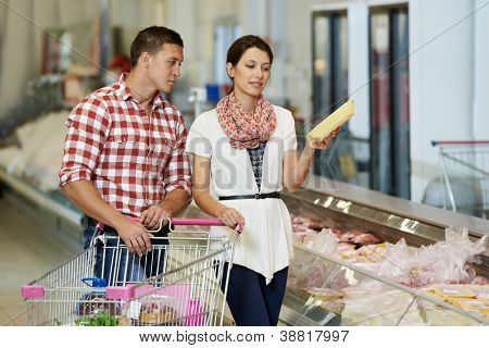 Young Family couple choosing bio food chicken meat in grocery supermarket during weekly shopping