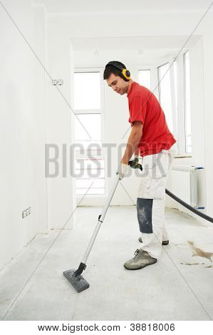 Worker cleaning floor with vacuum cleaner from industrial concrete dust and cement dirt during home renovation work