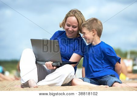 Mother and little boy smiling with laptop at vacation on sea beach resort