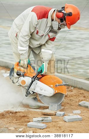 construction worker at curb stone cutting work by cut-off disc saw with diamond wheel