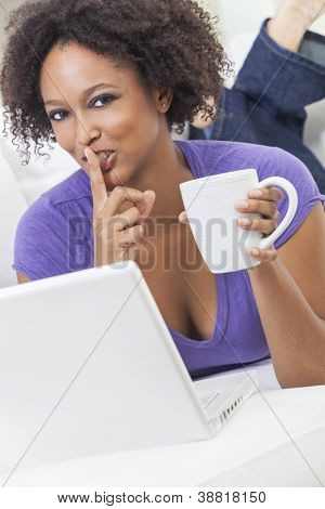A beautiful happy mixed race African American girl or young woman laying down on sofa using a laptop computer drinking coffee & holding finger to her lips