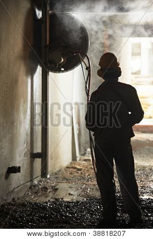 builder worker in safety protective equipment operating construction machine during industrial demolition