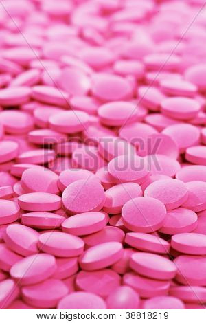 Pharmacy theme, Heap of pink round medicine tablet antibiotic pills. Shallow DOF
