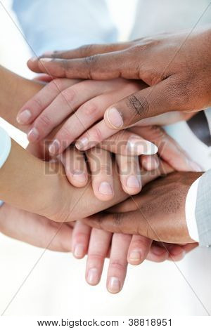 Vertical image of pile of hands of business partners