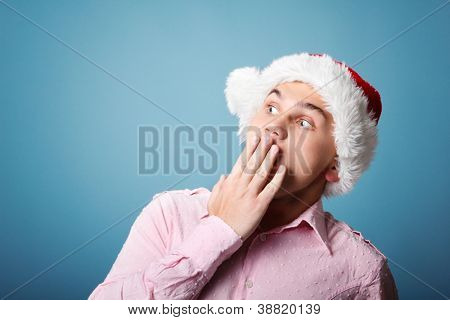 surprise young cheerful christmas man with santa's hat over blue background