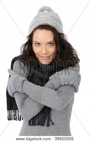 Beautiful woman feeling cold in winter, wearing scarf cap and gloves, isolated on white.