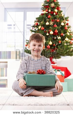 Portrait of happy little kid sitting in pyjama in christmas morning holding gift parcel, smiling at camera.