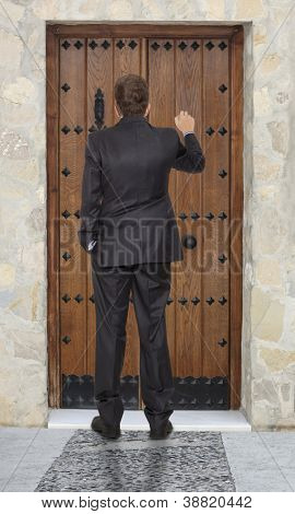 Businessman knocking at a wooden door